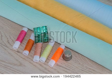 Sewing tools and sewing kit on wooden textured background. Sewing kit. Thread needles and cloth