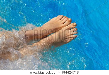 Bare Feet Of Woman On The Pool Water