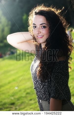 Portrait of a beautiful young girl with a slight smile. Curly hair, arm above the head. Outdoor in a green park.