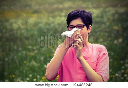 Young boy with pink t-shirt blowing his nose outdoors in mountains and vintage effect