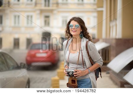 Happy young woman traveling in Europe.Girl with long brown hair smiling and holding camera in her arms.