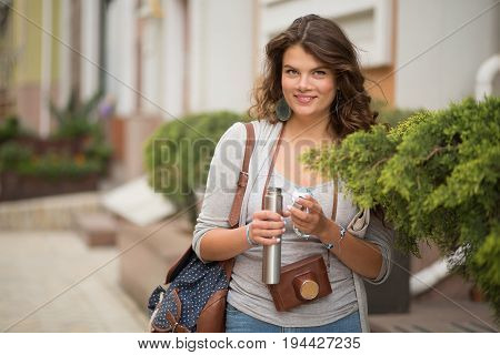Portrait of young woman travelling in european city. Long haired girl smiling and holding thermos bottle, dhot made with wide opened diaphragm.