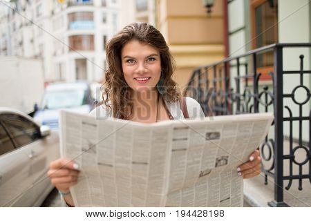 Young smiling tavel girl holding newspaper. Attractive female with long curly hair and brown eyes standing in the street with newspaper.