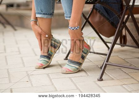 Close up view on tired legs of tourist woman. Girl sitting and relaxing after promenade, her legs are hurting.