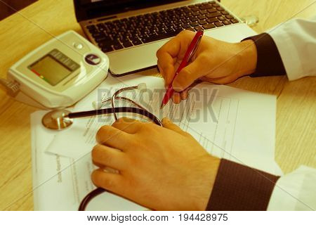 Male doctor with stethoscope sitting at a desk writing something prescription or recommendation of the patient the photo. Concept photo doctor - Retro color