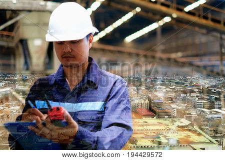 Double exposure of city background and engineer with uniform and white safety helmet working in the production line process plant, industrial concept