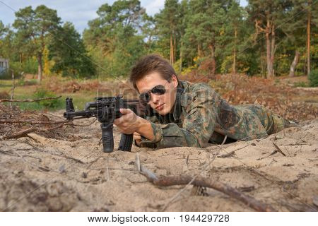 Teenager boy lying in his battle dress sunglasses and a rifle Air Soft Gun