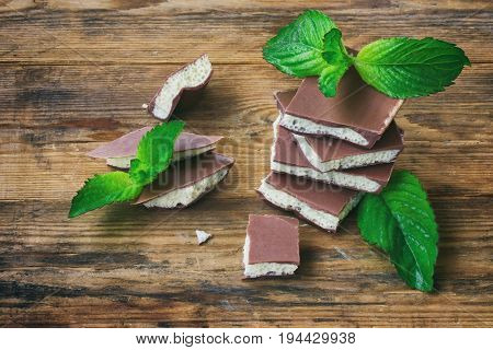 Milky porous white and dark chocolate with mint leaves on wooden table