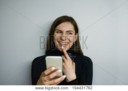 Headshot of attractive cheerful young female with long dark hair and braces texting messages using online messenger on her mobile phone having flirty look touching lips and smiling broadly