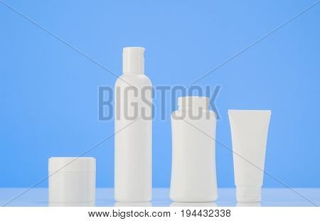 Set of tubes and containers of cream or gel in white plastic packaging. Product mockup with mirror reflection on white table with blue background.