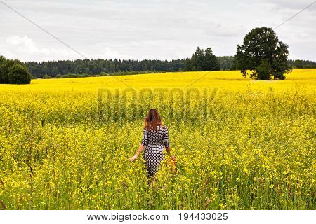 Young Beautiful Woman In A Flowering Rapeseed Field