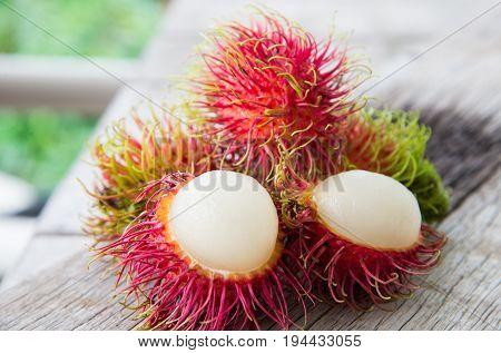 Fresh red rambutan Thai fruit on wood texture.