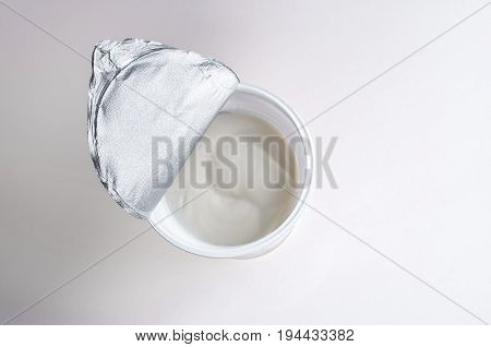 Top view of plastic container with tasty dessert or white sour cream isolated on white background