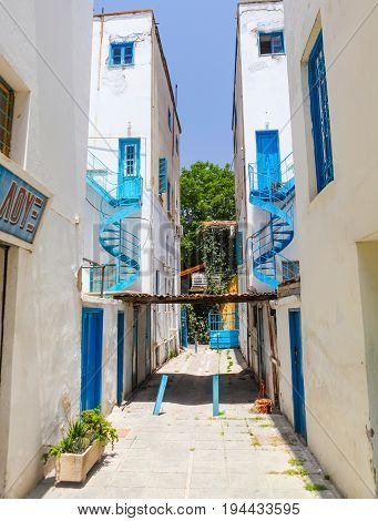 NICOSIA CYPRUS - MAY 30 2014 : View on the narrow street and white houses with blue iron helical stairs'
