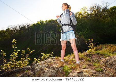Woman backpacker standing and enjoying the view in forest on the path during sunny day. Travel hiking backpacking tourism and people