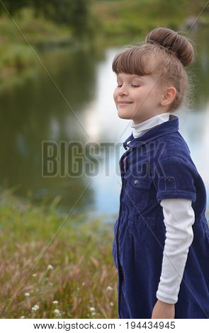 Adorable little girl with beautiful brown hair taking a deep breath with closed eyes and smile on lake background