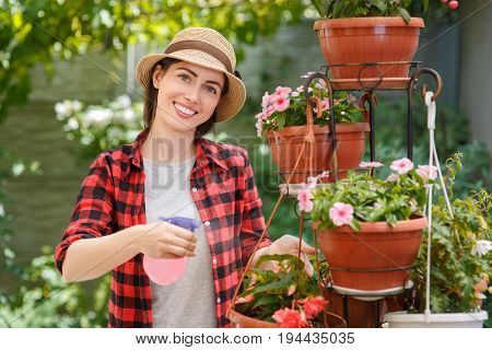 portrait of happy young woman gardener spraying water on plants. Girl with sprayer bottle spraying pesticide on her flowers. People, gardening, care of flowers, hobby concept