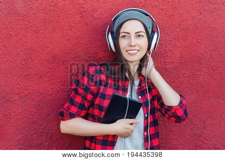 Portrait of happy hipster woman holding tablet computer and listening music in headphones. Girl using digital tablet outdoors. Technology, music, lifestyle, and millenial people concept. Hipster style poster