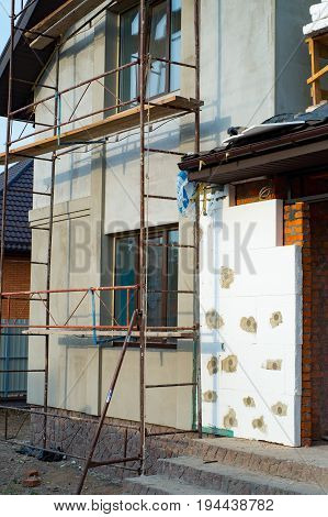 Reconstruction of private house installing thermal insulation for walls with scaffoldings