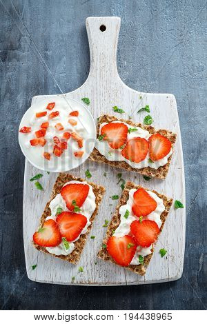 Homemade Crispbread toast with Cottage Cheese and Strawberry on white wooden board