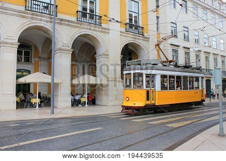 LISBON, PORTUGAL - JUNE 7, 2017: Lisbon yellow tram on the way to Commerce Square in old town Lisbon, Portugal. Famous typical tourist travel attraction on sunny summer day. Colorful architecture city buildings street background view
