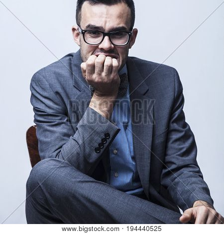 Problems in business. Young nervous businessman biting his nails fingers with worried expression