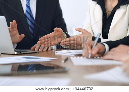 Group of businesspeople or lawyers discussing contract papers and financial figures while sitting at the table. Close-up of human hands at meeting or negotiations. Success and communication concept.
