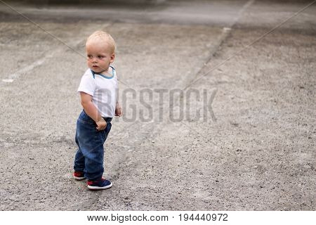 Cute Blonde Kid Looking Looking Back. Awesome Baby Boy On The Walk. Copy Space