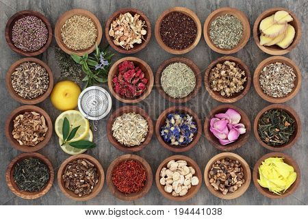 Healthy herb tea selection in wooden bowls and loose with strainer, teas also used in alternative medicine.