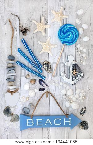Abstract collage of beach sign, seashells, pearls, decorative seaside objects, driftwood and rock candy on distressed white wood background.