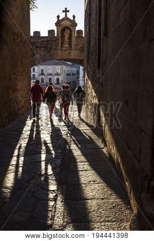 Caceres Spain - July 1 2017: Tourists walking under Star Arch or Arco de la Estrella Caceres. Sunset light