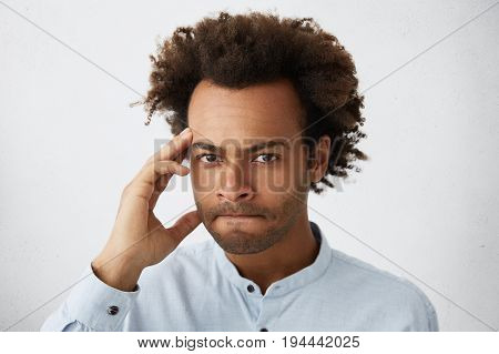 Headshot Of Skeptical Male With Dark Skin And African Curly Hairstyle Looking With Hesitation In Cam
