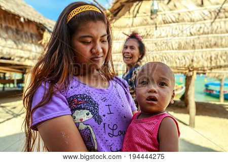Mu Ko Surin National Park, Thailand - Jannuary 3, 2016:Portrait of young woman holding her amazed baby with eyes wide open in their village. Family of Moken ethnic, also called Chao Ley, Sea Gypsies.