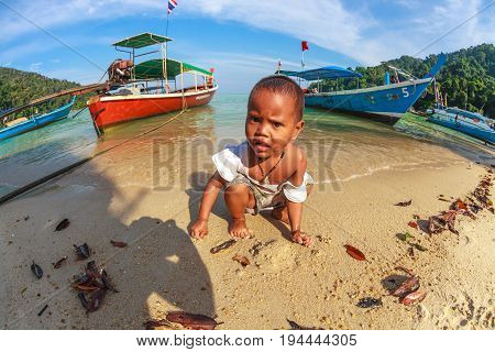 Mu Ko Surin National Park, Thailand - January 3, 2016: Sad lone child of Chao Leh or Moken tribe, playing on the beach of his village. Colored long-tail boat on background.