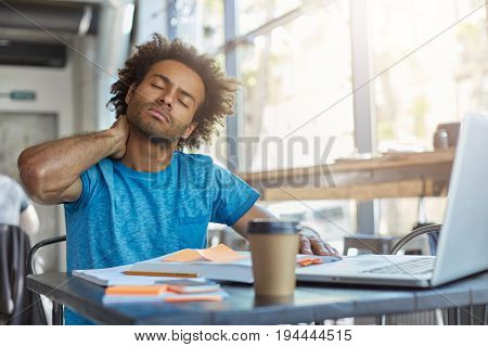 Young Tired Manager Sitting In Restaurant Surrounded With Papers And Laptop Computer Having Tired Lo