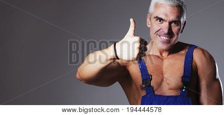 young strong handsome man builder with muscular athletic strong body