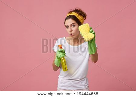 Young Woman Wearing Working Clothes Standing With Sponge And Detergent Having Careful Look Posing Ag