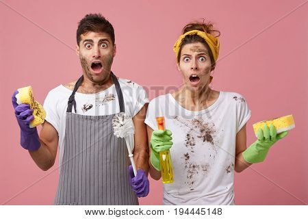 Handsome Male Wearing Apron Standing Near His Wife Holding Cleaning Equipment Having Shocked Look. C