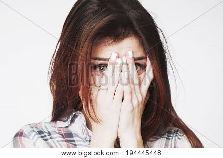 Portrait of a young woman looking in fear (Gestures body language psychology)