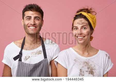 Studio Portrait Of Smiling Man And Woman In White T-shirts Being Dirty After Cleaning Their Apartmen