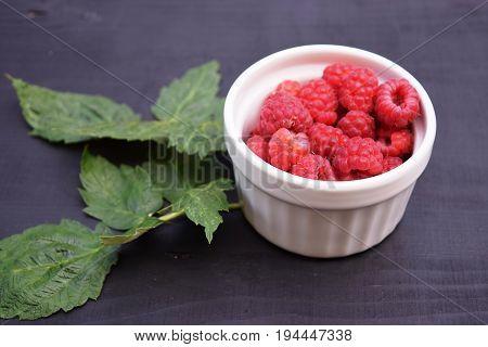 Ripe and tasty raspberries on a wooden background. Raspberries on wooden table .Fresh , vitamins healthy food vegan ingredients.