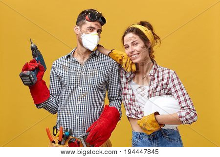 Professional Male Manual Worker Wearing Protectibe Eyewear On Head, Mask And Gloves Holding Drilling