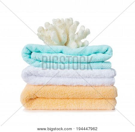Beautiful large white sea coral on the stack of yellow blue and white fluffy terry towels isolated on a white background