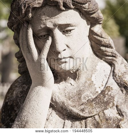 Antique statue of woman on tomb as a symbol of depression and sorrow