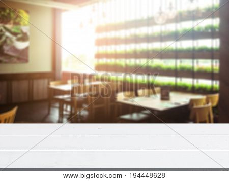 Abstract blur and defocused restaurant and cafe interior for background and empty wooden table space platform for present product.