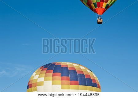 Colorful hot-air balloon ready to get up in flight and another already in flight against a blue sky