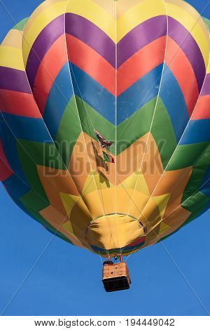Colored hot-air balloon in flight against a blue sky
