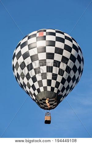 Black and white balloon in flight against a blue sky