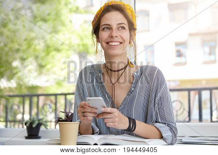 Outdoor Portrait Of Beautiful Female In Casual Clothes Sitting At Terrace Reading Book, Drinking Del
