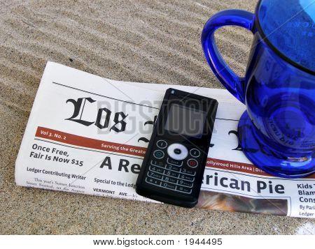 Close Up Shot Of Newspaper, Phone And Mug On The Sand